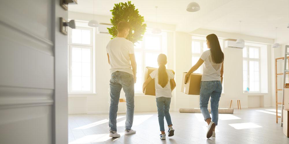 Familie mit Kartons ziehen in eine Wohnung ein