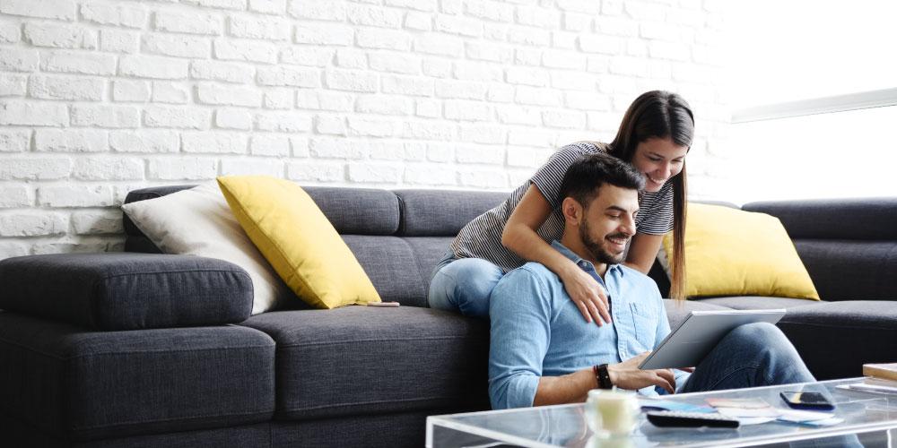 Ein Pärchen mit Laptop auf einem Sofa