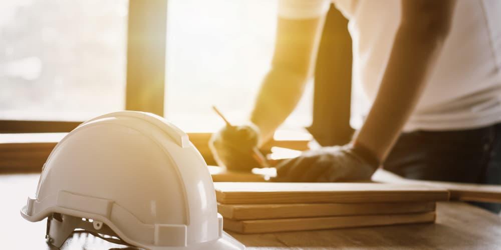 Mann sieht sich die Pläne der Immobilie an, er will durch Eigenleistung Kosten sparen