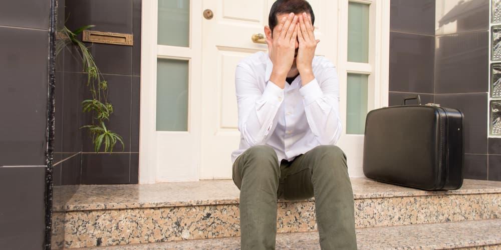 Ein Mann trennt sich von seiner Frau und sitzt vor der Tür vom gemeinsamen Haus, die Scheidung steht bevor