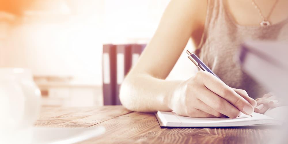 Eine Frau macht Notizen, um die richtige Anschlussfinanzierung herauszufinden