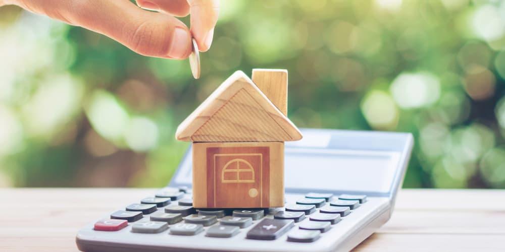 Ein Bild mit Taschenrechner und einem Haus, welche Betriebskosten fallen nach dem Hauskauf an?