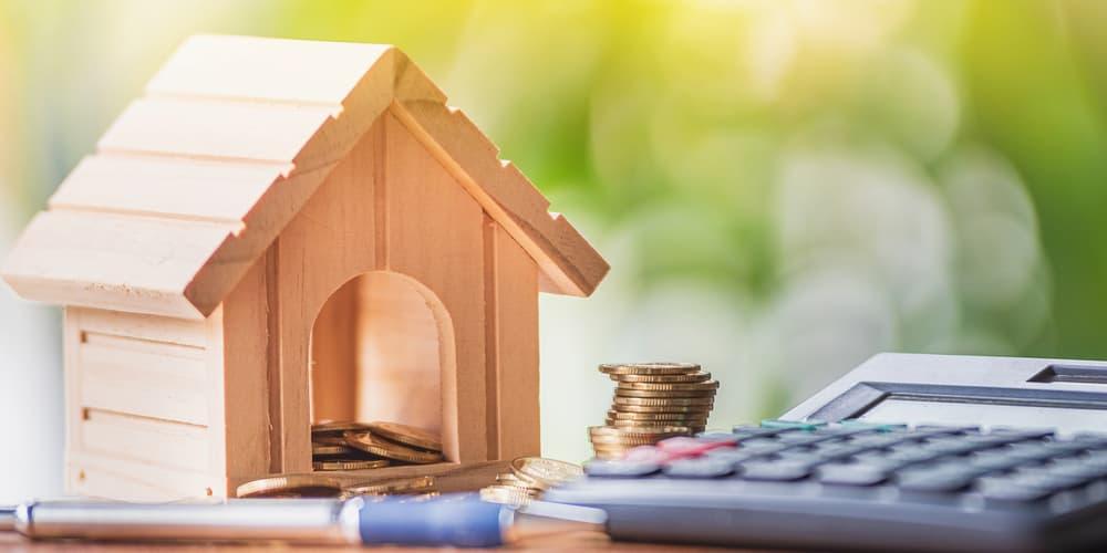 Ein Haus mit Taschenrechner und Münzen, Symbolbild für Nebenkosten beim Hauskauf