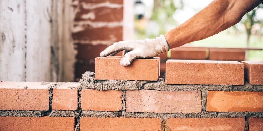 Ein Mann legt Ziegel übereinander, davor schloss er ein Baudarlehen ab