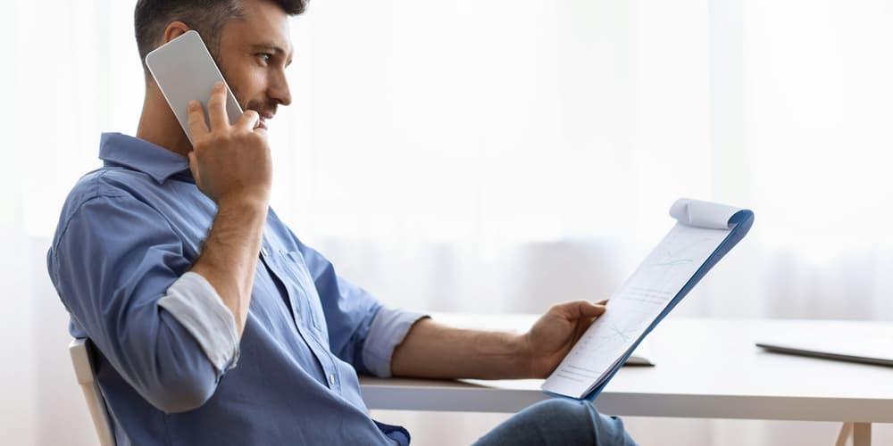 Ein Mann telefoniert mit der örtlichen Behörde um Informationen über das Baulastenverzeichnis zu erhalten