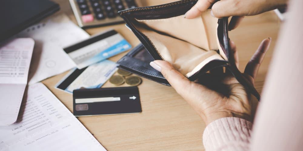 Eine Frau blickt in eine leere Geldbörse, was tun bei einem finanziellen Engpass?