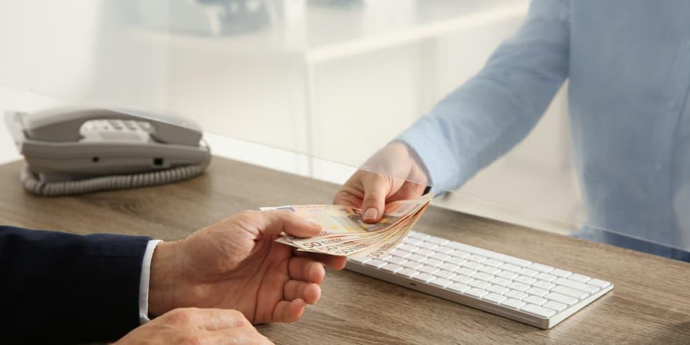 Ein Mann zahlt eine Nichtabnahmeentschädigung an die Bank
