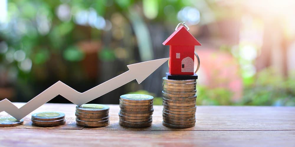 Modell mit einem Haus, Münzen und einem Pfeil, wie entwickeln sich die Immobilienpreise?