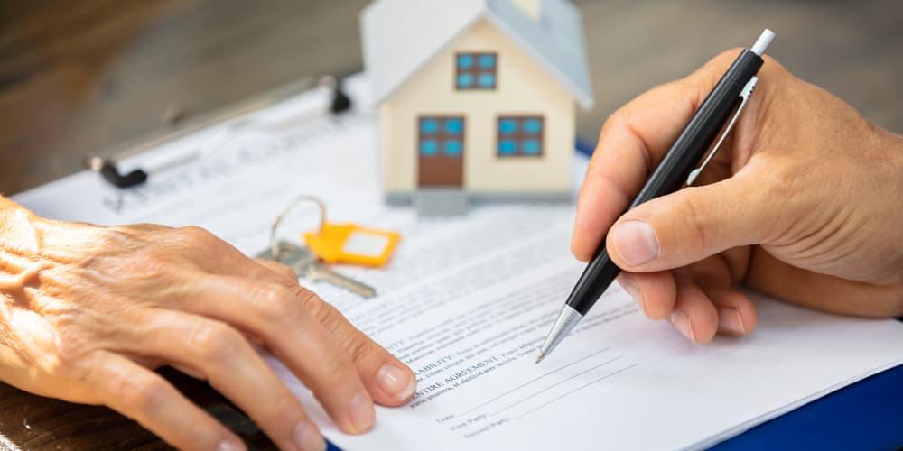 Ein Mann unterzeichnet einen Kaufvertrag für ein Haus.