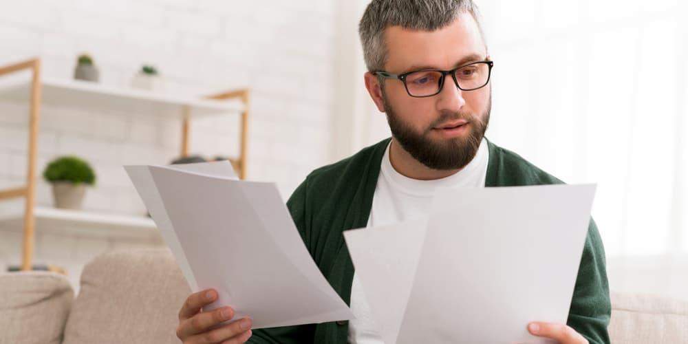 Baufinanzierung über Versicherung – Ein Mann vergleicht Angebote.