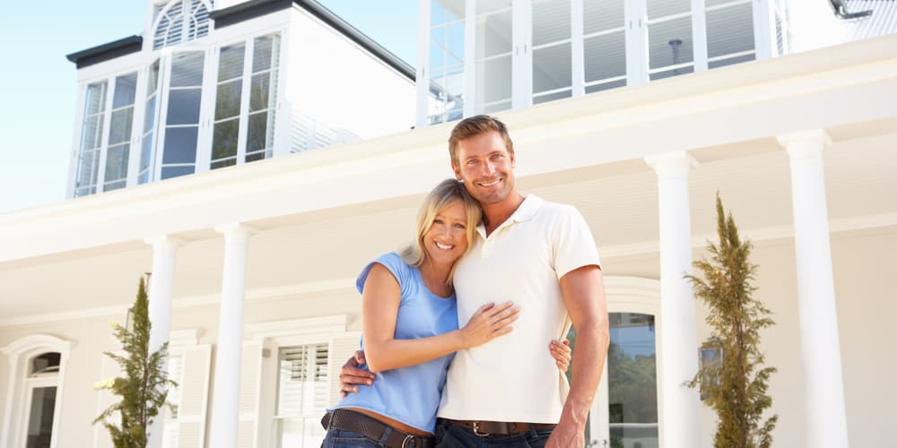 Ein Paar vor einer neuen Immobilie, wie ist der Ablauf einer Baufinanzierung?