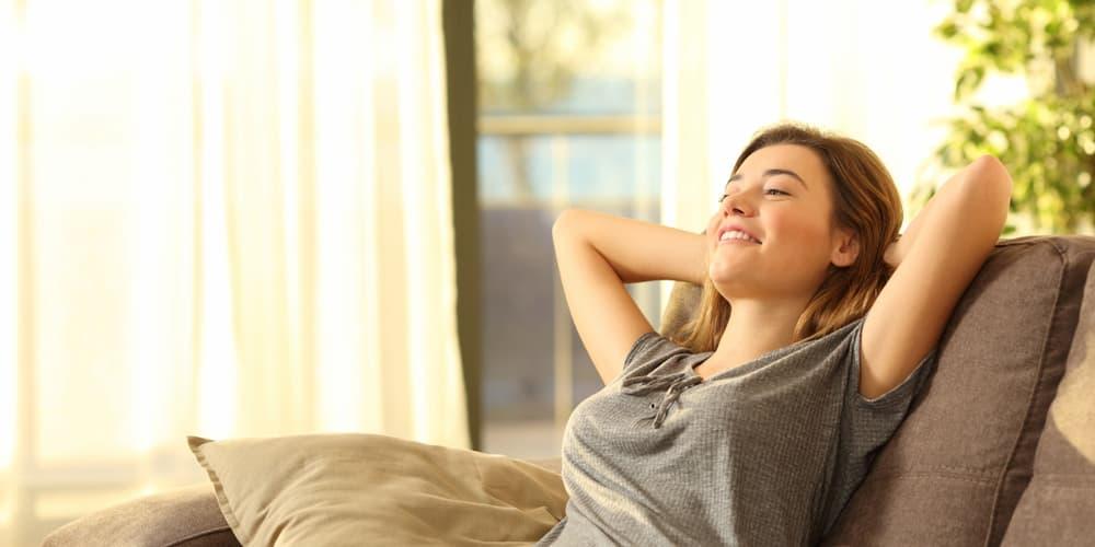Eine Frau sitzt entspannt Zuhause, sie ist Single und hat eine Baufinanzierung