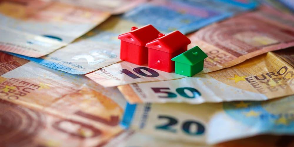 Geldscheine und Modellhäuser symbolisieren die Kosten beim Hauskauf.