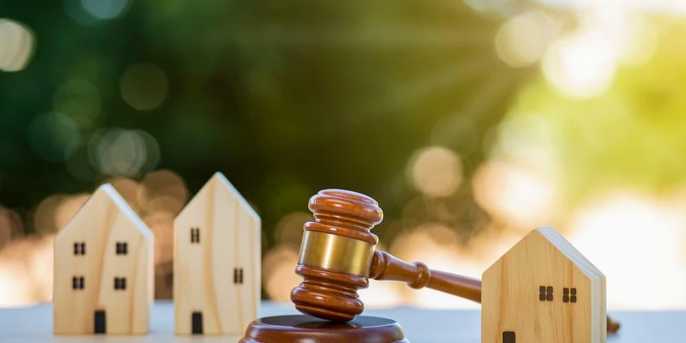 Mehrere Holzhäuser und ein Richterhammer als Symbolbild für das Wohnrecht