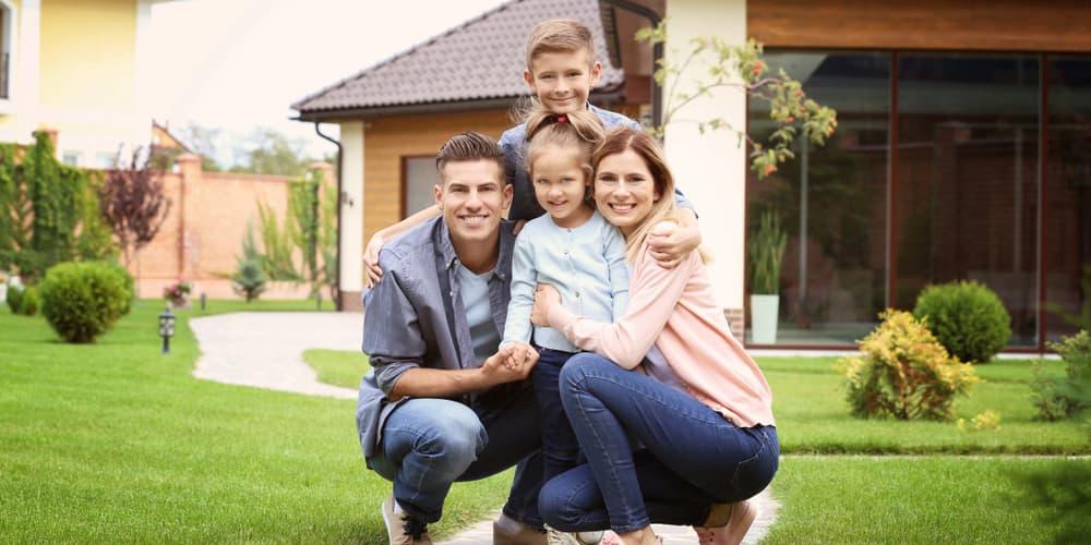 Eine Familie vor ihrem Haus, sie hat gravierendeFehler bei der Eigenheimfinanzierung vermieden